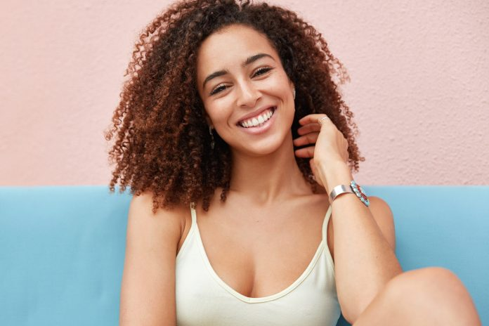 Photo of positive smiling woman with broad charming whiten teeth smile dressed casually and recreats at home, feels relaxed and comfortable, happy to hear good news from friend. People, ethnicity, happiness