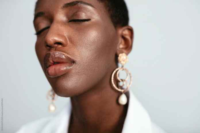 Black woman with full, plump lips and gloss.