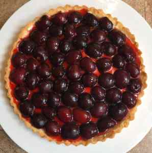 tart shell with cream, sliced cherries and cherry sauce