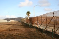 The empty space between the border fences.