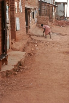 Child sweeping in Acholi Quarters.