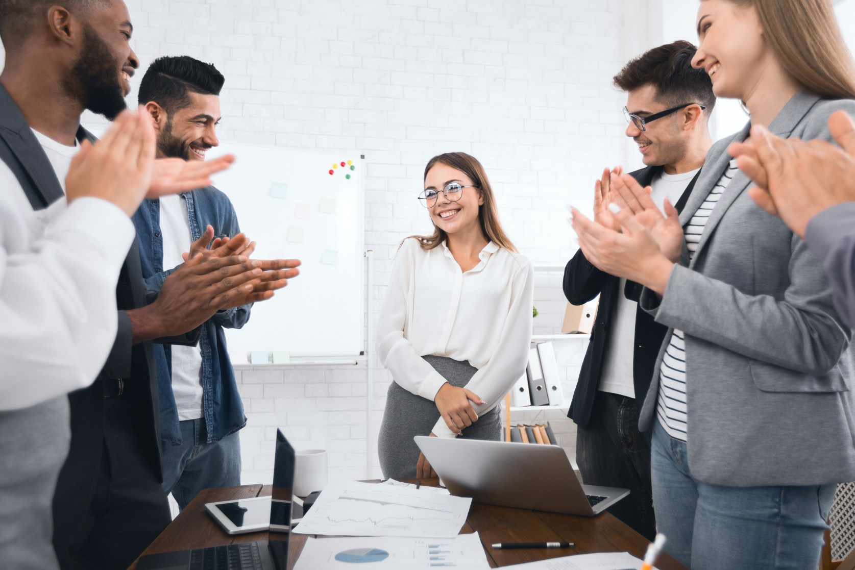 Business team congratulating successful female manager with applause at conference meeting