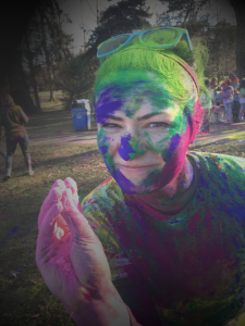 Emily Kocian-Dery with green, purple, pink and blue colored powder