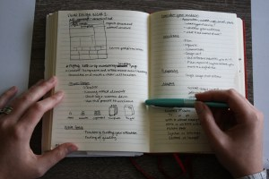 Hands on notebook with blue pen