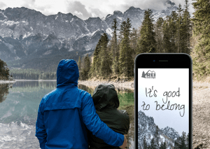 Outdoors with snow capped mountains and lake, trees, two people standing by lake, black iPhone 6 in foreground with REI landing page redesgin