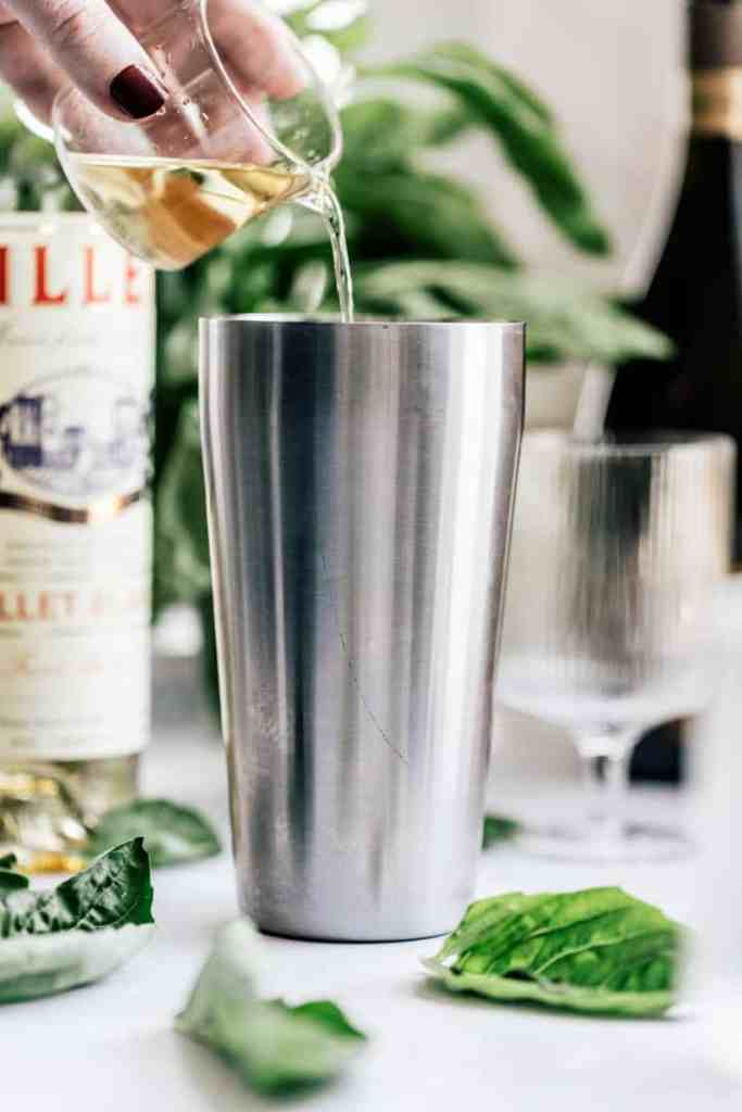 Pouring Lillet to make a Basil Spritz