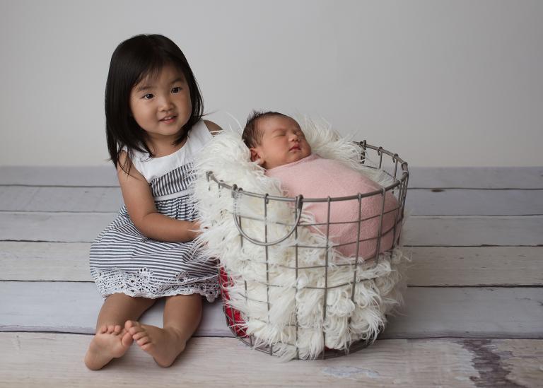 newborn baby girl in basket, big sister