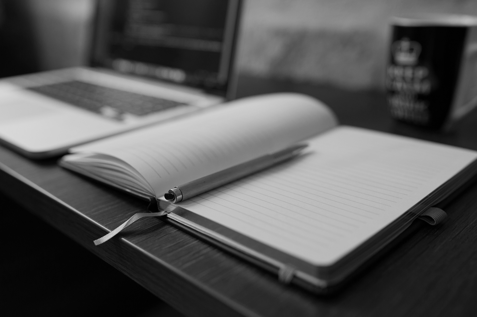 black and white photo of an open notebook beside a laptop