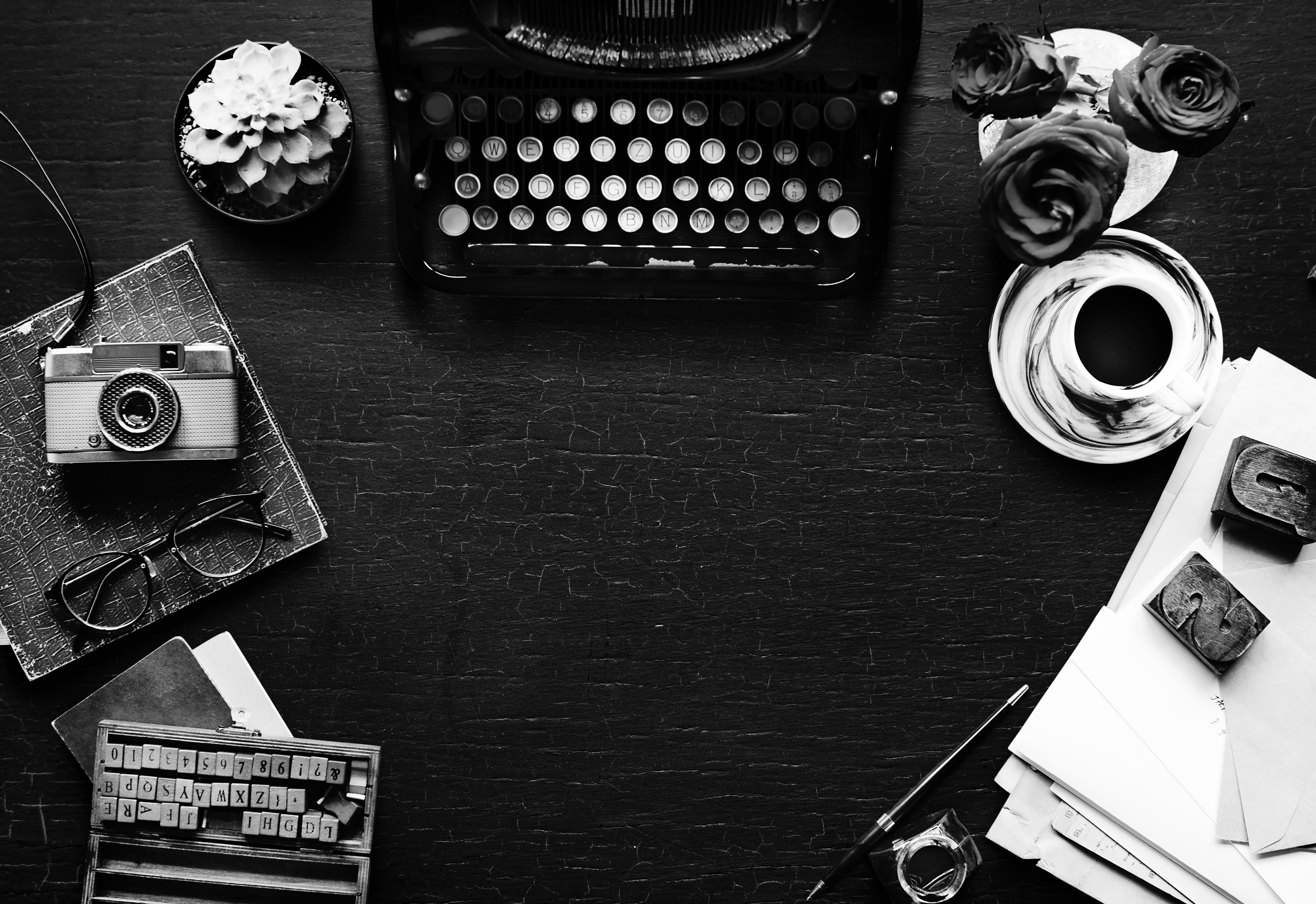 a desk with a typewriter, camera, and other items
