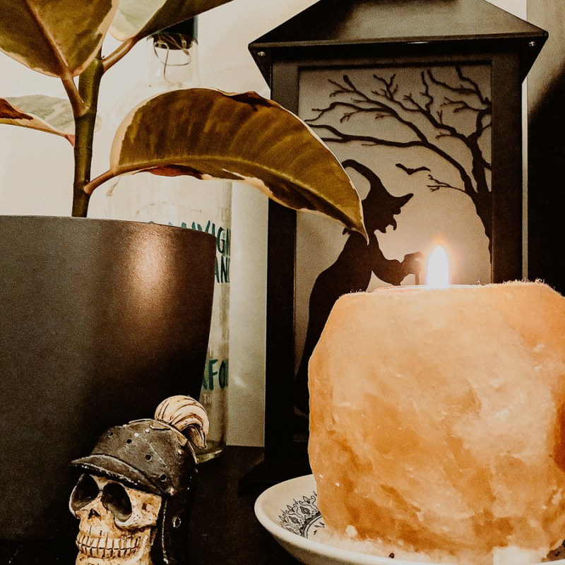 Easy Autumnal Home Decor DIY Ideas display featuring a skull ornament, witchcraft lamp, plant, fairy lights in a bottle, and a himalayan salt candle.