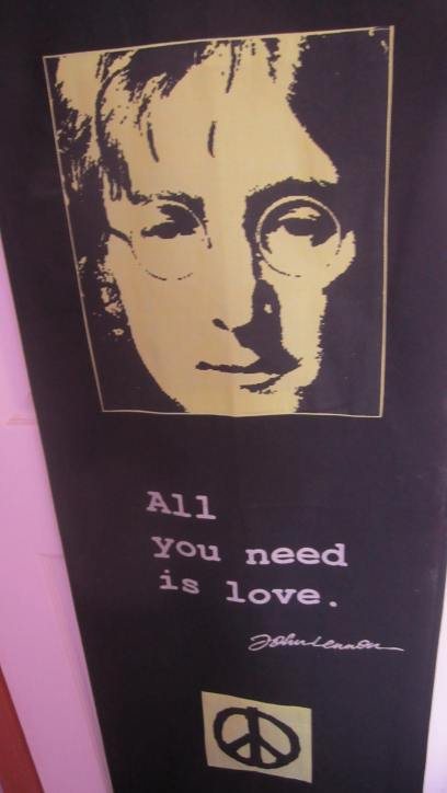 """A black poster with a green print of John Lennon that says """"All you need is love"""" and a peace sign"""""""
