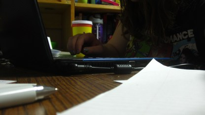 Emily Stewart typing on a blue laptop while wearing a black t-shirt