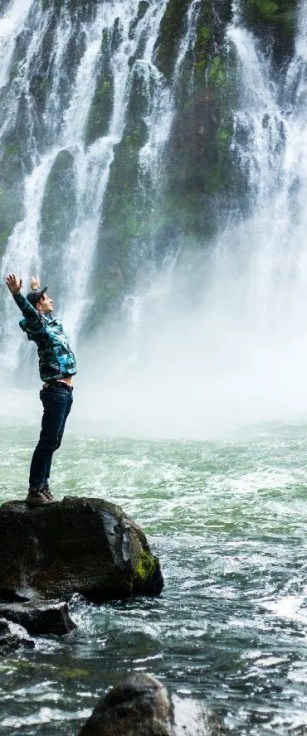 Person who wants to live standing next to a waterfall with his arms stretched up.