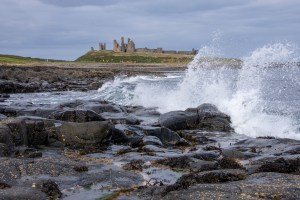 Waves and Dunstanburgh Castle
