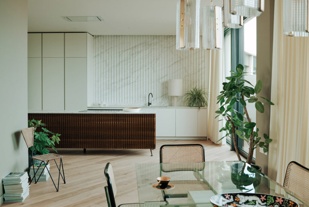 Cane dining chairs set against the pared down kitchen. Photo: Michael Sinclair