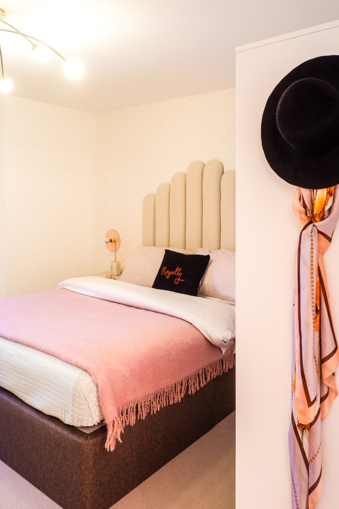 modern London apartment with pink bedroom and curved headboard