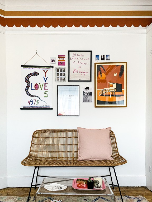 gallery wall above rattan bench