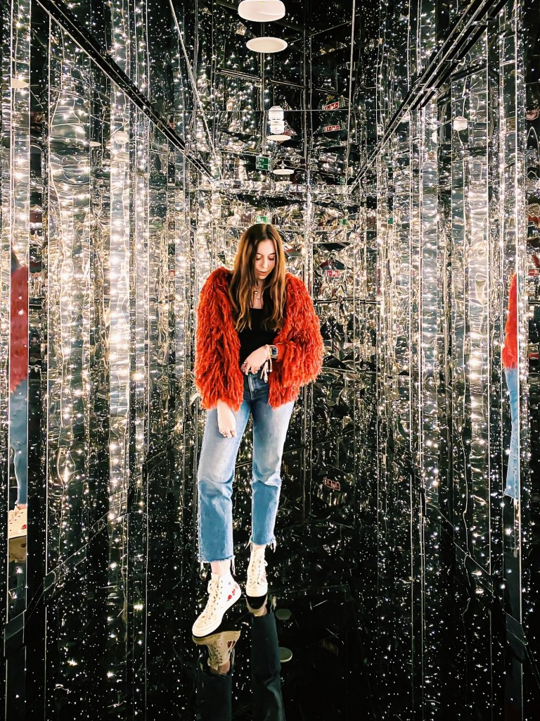 girl in red fluffy jacket in mirror and lights corridor