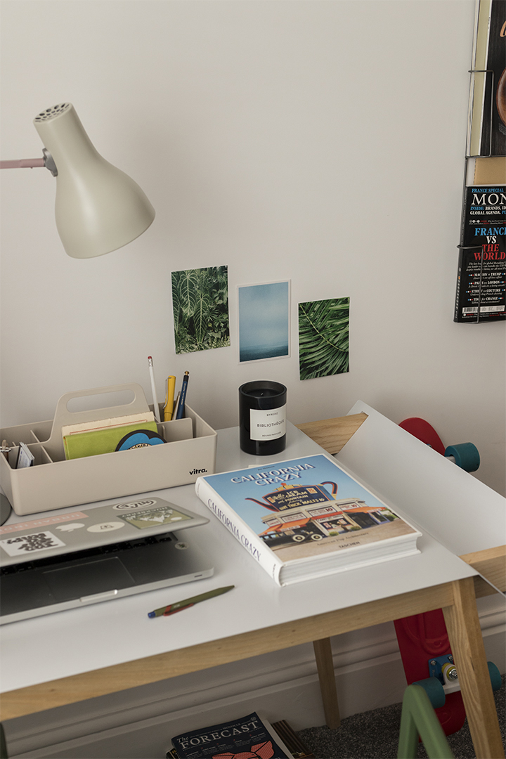 minimal office desk with postcards on the wall