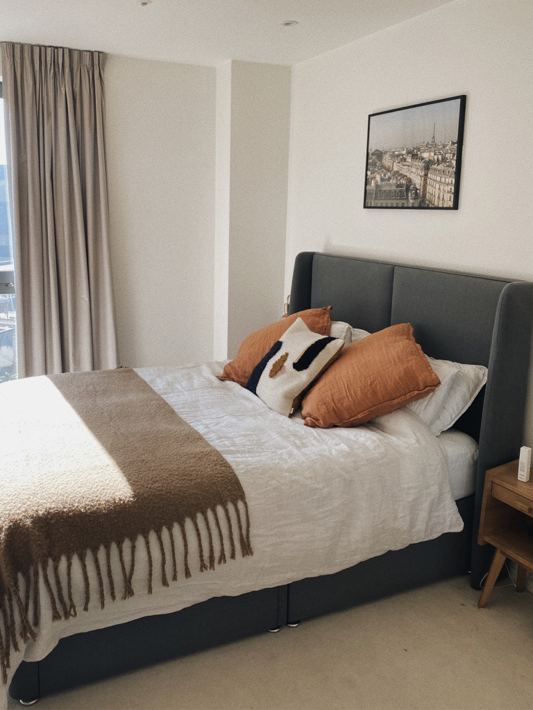 bedroom with gray bed, white linen and rust cushions