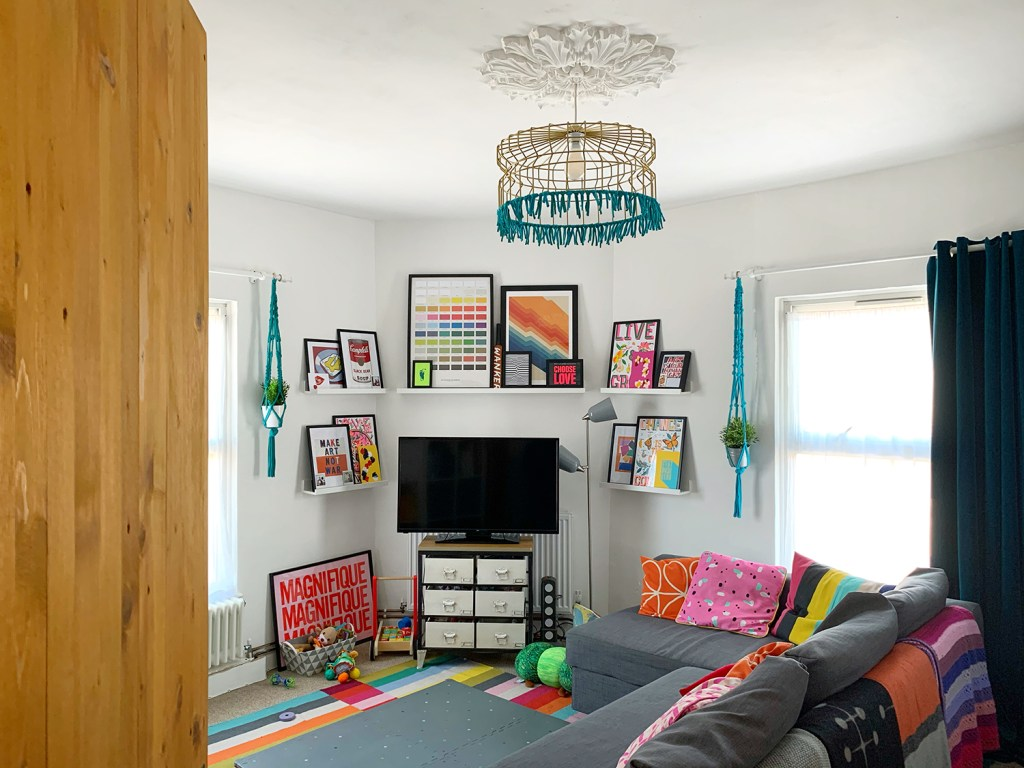 a white living area with colourful art.