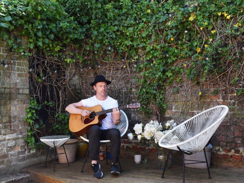 guy plays guitar in outdoor space