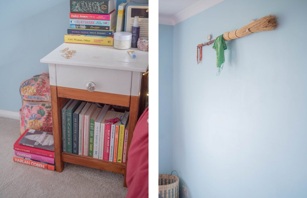 bedside table with books and broom on wall