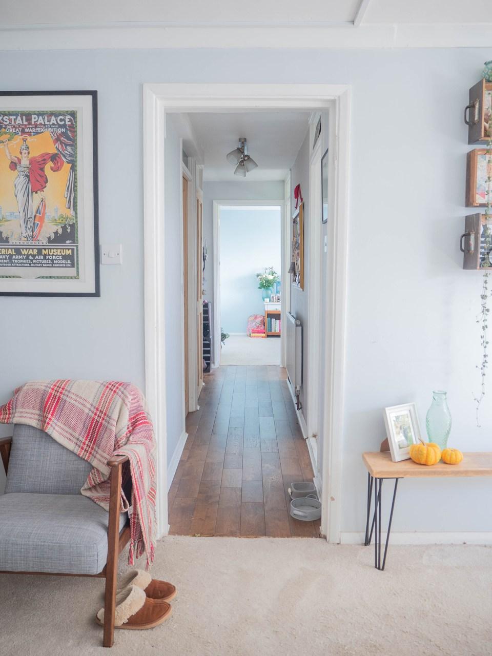 gray hallway with wooden floor leading to bedroom