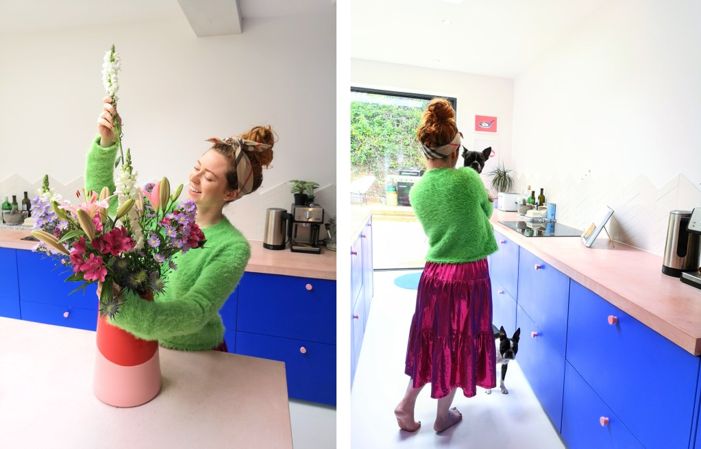 girl in pink and blue kitchen with two boston terriers