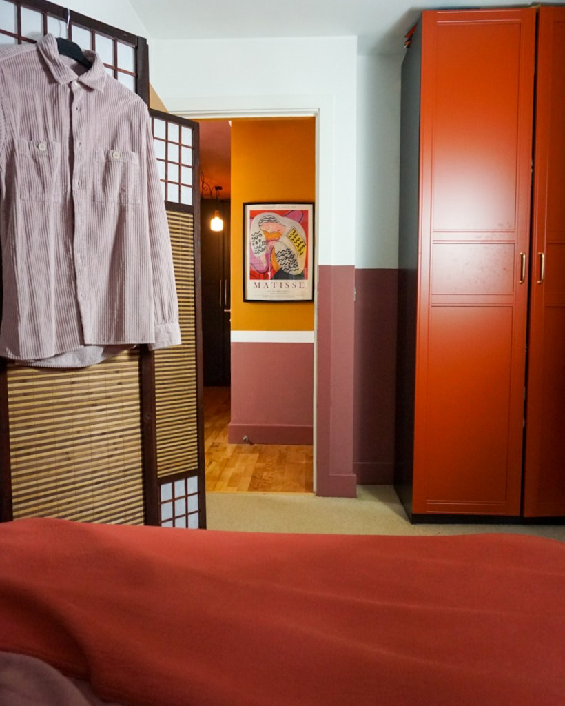 red themed bedroom with rattan screen