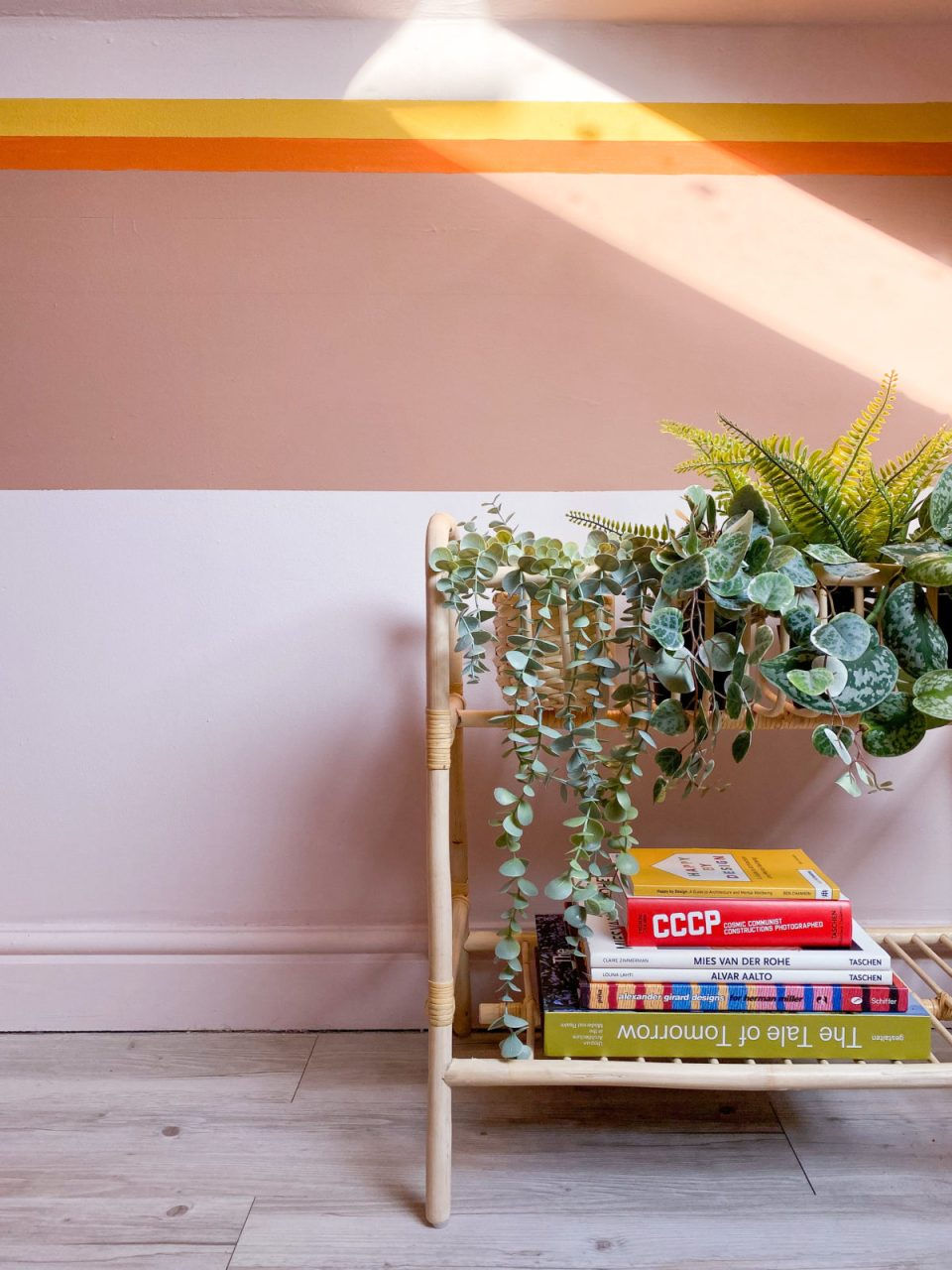 rattan magazine rack and plant stand with faux plants and books.