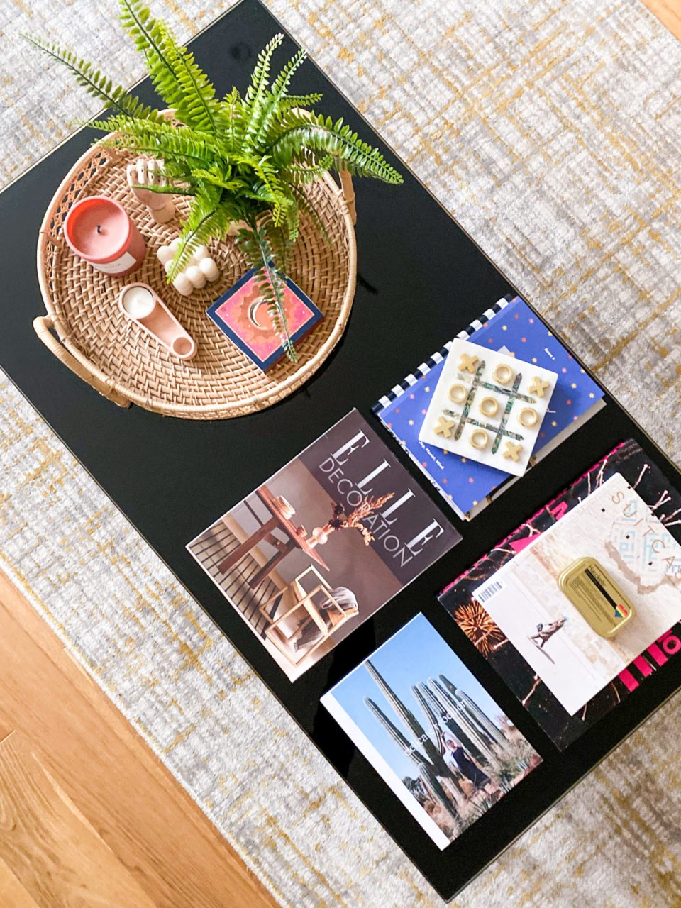 black coffee table covered in rattan table tray, magazines and a game of noughts and crosses