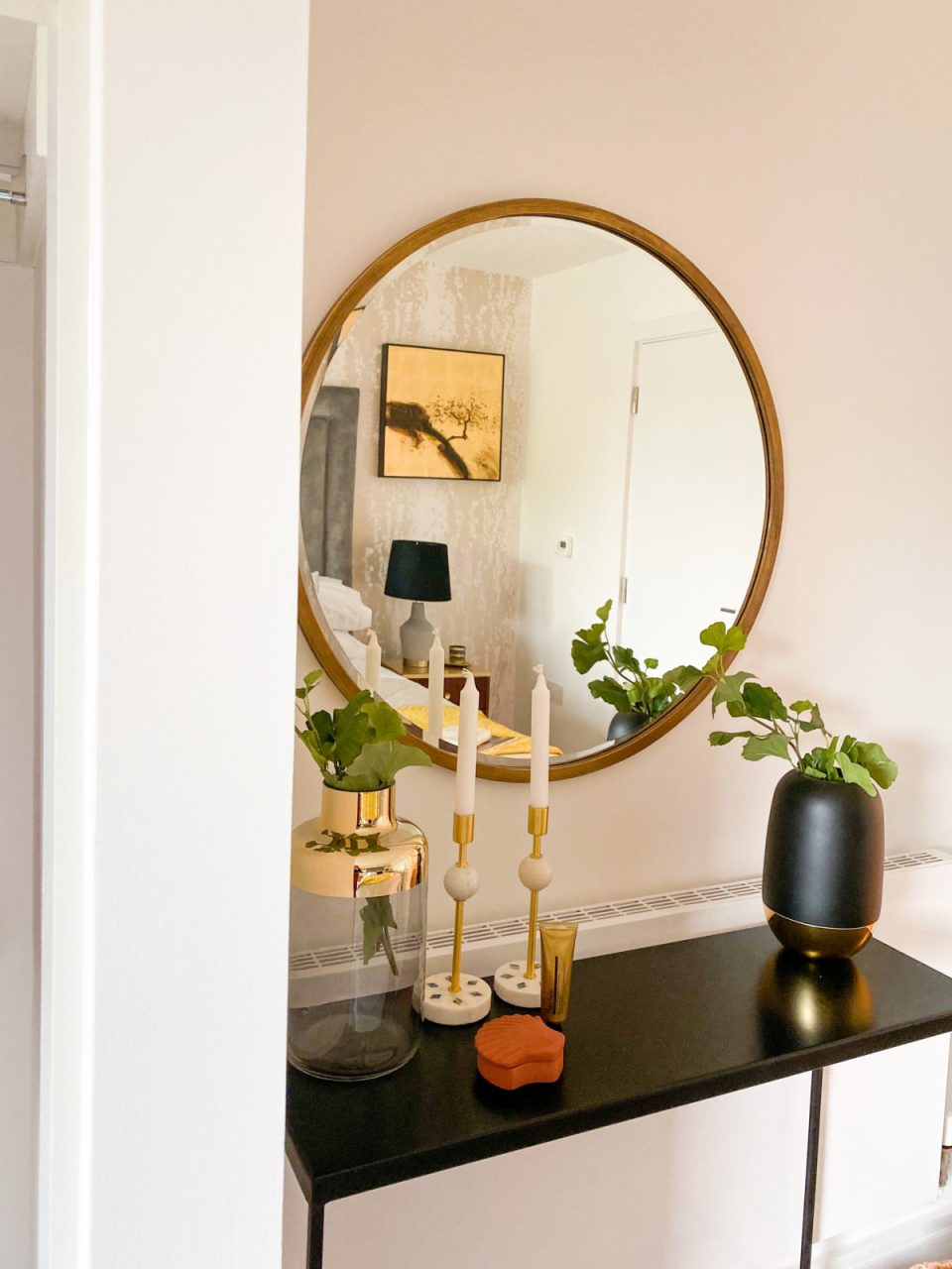 bedroom console table with candlesticks, vases and large mirror