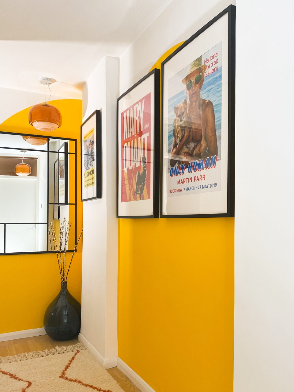 yellow and white mid-century hallway with exhibition artwork