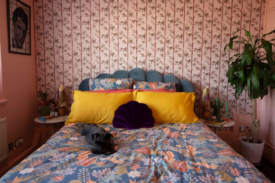 coral pink bedroom with bamboo wallpaper and scallop bed