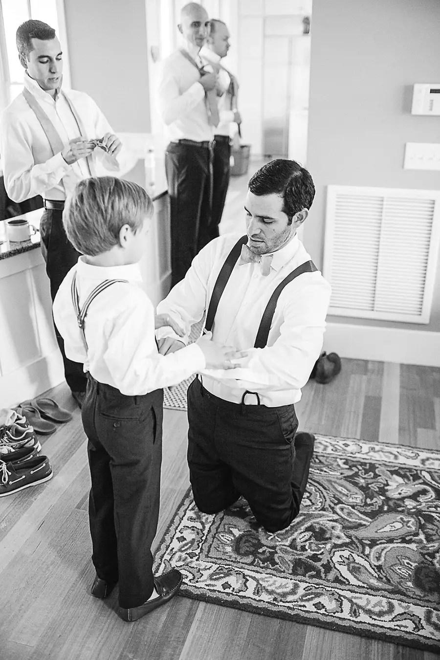 The Groom Helping the Ring Bearer Get Ready - Bald Head Island Wedding - Photo by Eric Boneske