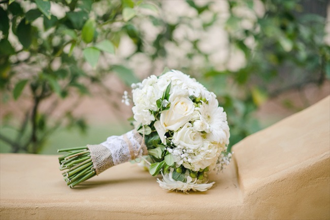 the bouquets and boutonnieres were filled with white roses; the bride's bouquet also featured white gerbera daisies