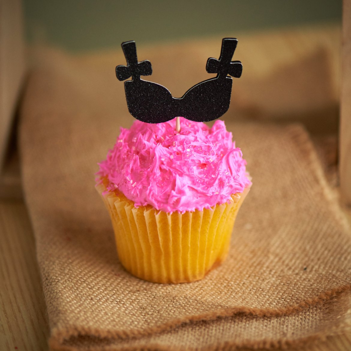 black bra cupcake toppers on hot pink cupcake by confetti momma party | fun bachelorette party ideas | http://emmalinebride.com/planning/fun-bachelorette-party-ideas/