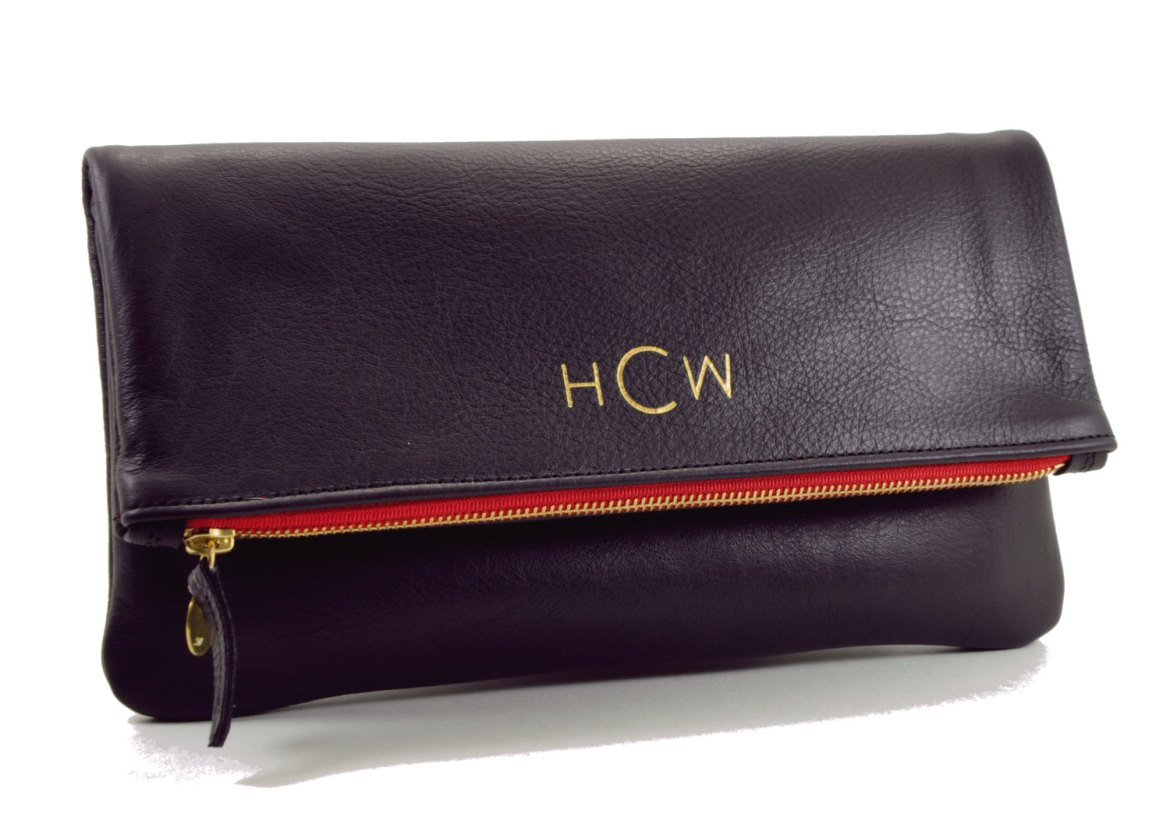 black foldover clutch with monogram in gold and red liner