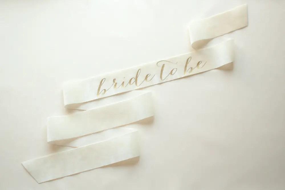 bride to be sash white with gold | stylish bachelorette sash ideas | via http://emmalinebride.com/bride/bachelorette-sash-ideas/