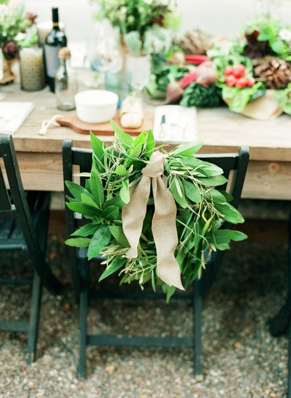 Use this chair wreath to decorate the backs of the bride and groom chairs at the wedding reception.  You can make it yourself with greenery, a wire frame, and burlap.