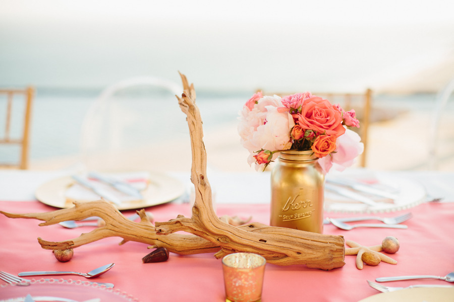 gold mason jar centerpieces with starfish and driftwood decor | photo: sara & rocky | via emmalinebride.com on how to decorate for beach wedding