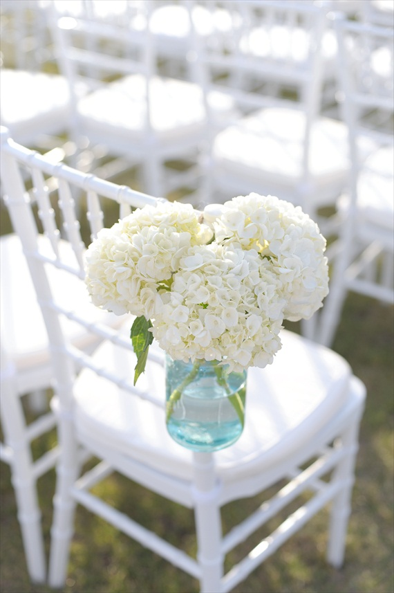 blue mason jars filled with white hydrangea flowers and attached to chairs hanging mason jar vases