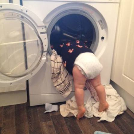 toddler leaning into a washing maching