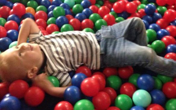 child in soft play ball pit