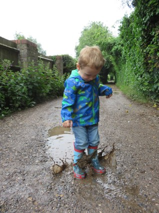 boy splashing in muddy puddles