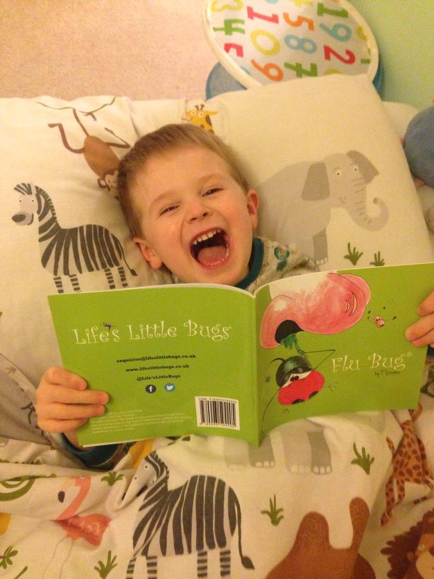 child in bed laughing reading flu bug from life's little bugs