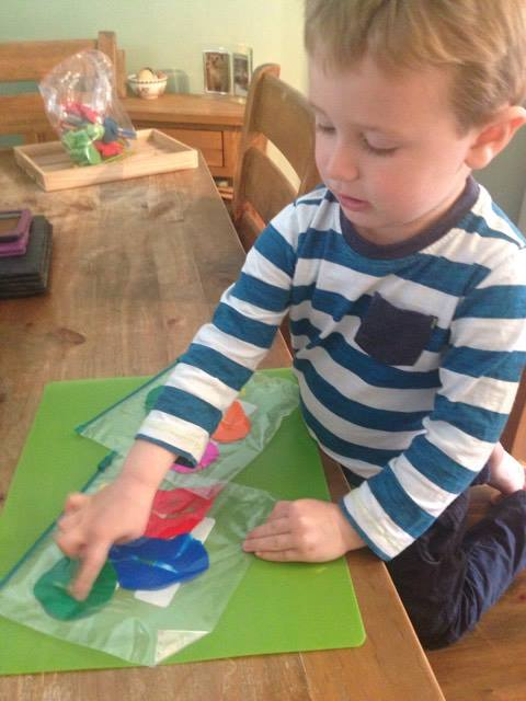 child pressing down on paint in a freezer bag