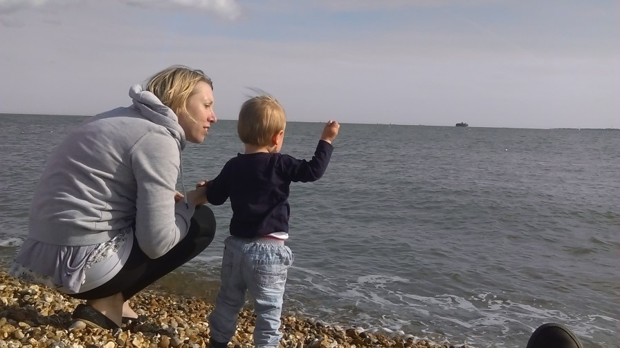 Mum and son throwing a stone in the sea