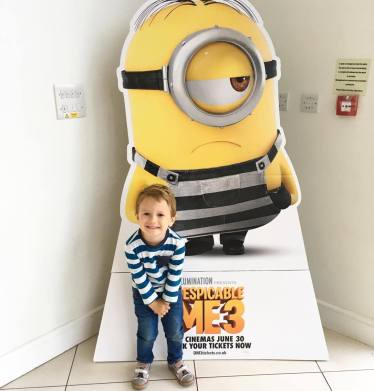 child in front of minions cardboard cut out